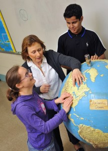 MSB female student explores raised globe with help of teacher