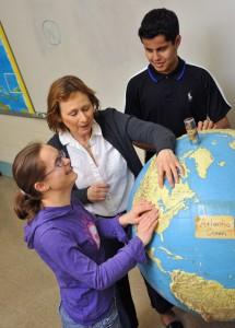 MSB female student explores raised globe with help of teacher