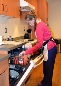 MSB female student loads dishwasher