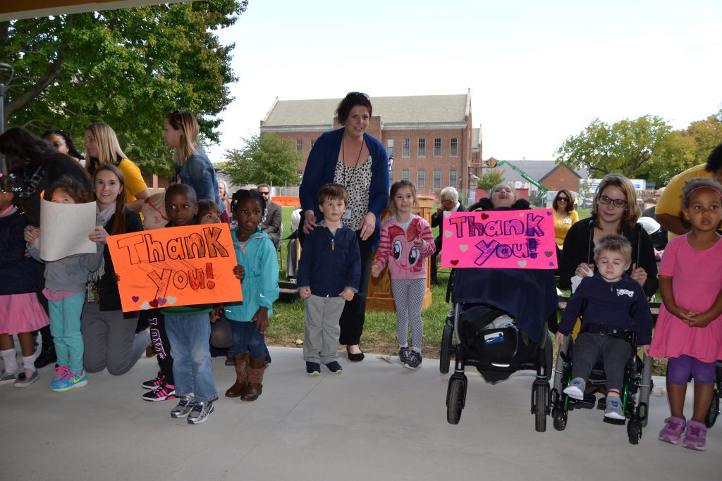 "Teachers and Standing children and adults and students and family members wheelchairs grouped together for a picture, holding two signs that read ""Thank You"""
