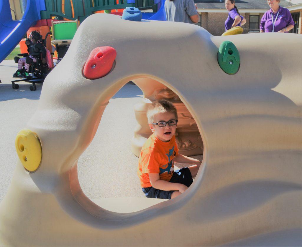Sam under playground tunnel