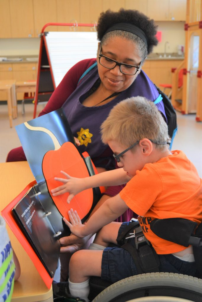 Student in wheelchair works with Paraeducator to feel textured book
