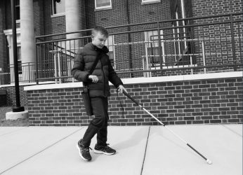 Student walks down the sidewalk with a walking stick