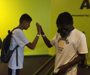 Two students giving a high five to one another