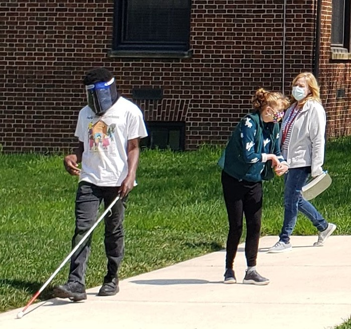 Student wearing PPE and walking with white cane