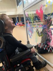 Young boy in wheelchair laughs at another boy on other side of decorated plexi-glass barrier