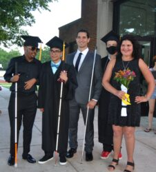 4 graduates pose with the commencement speaker