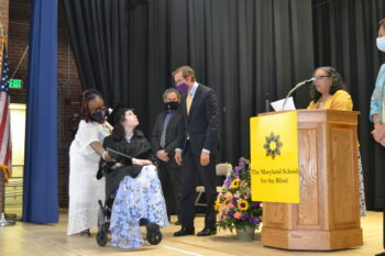 Student in wheelchair receiving her diploma