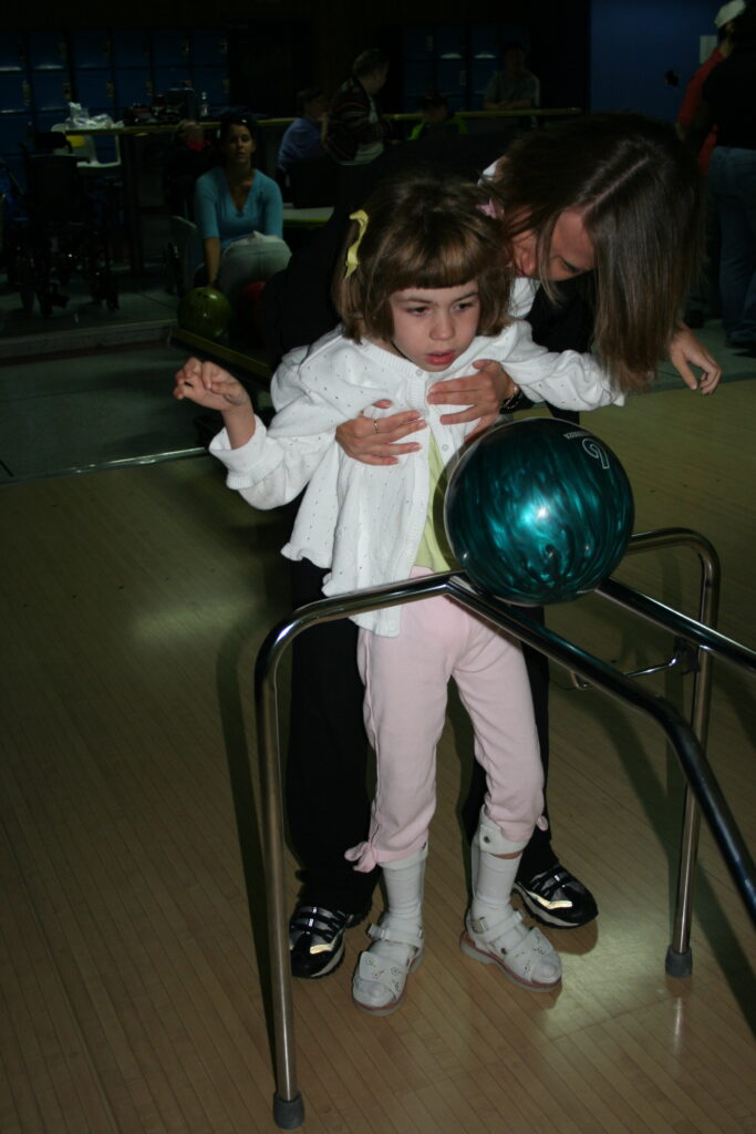 Young student using adapted bowling ramp to bowl